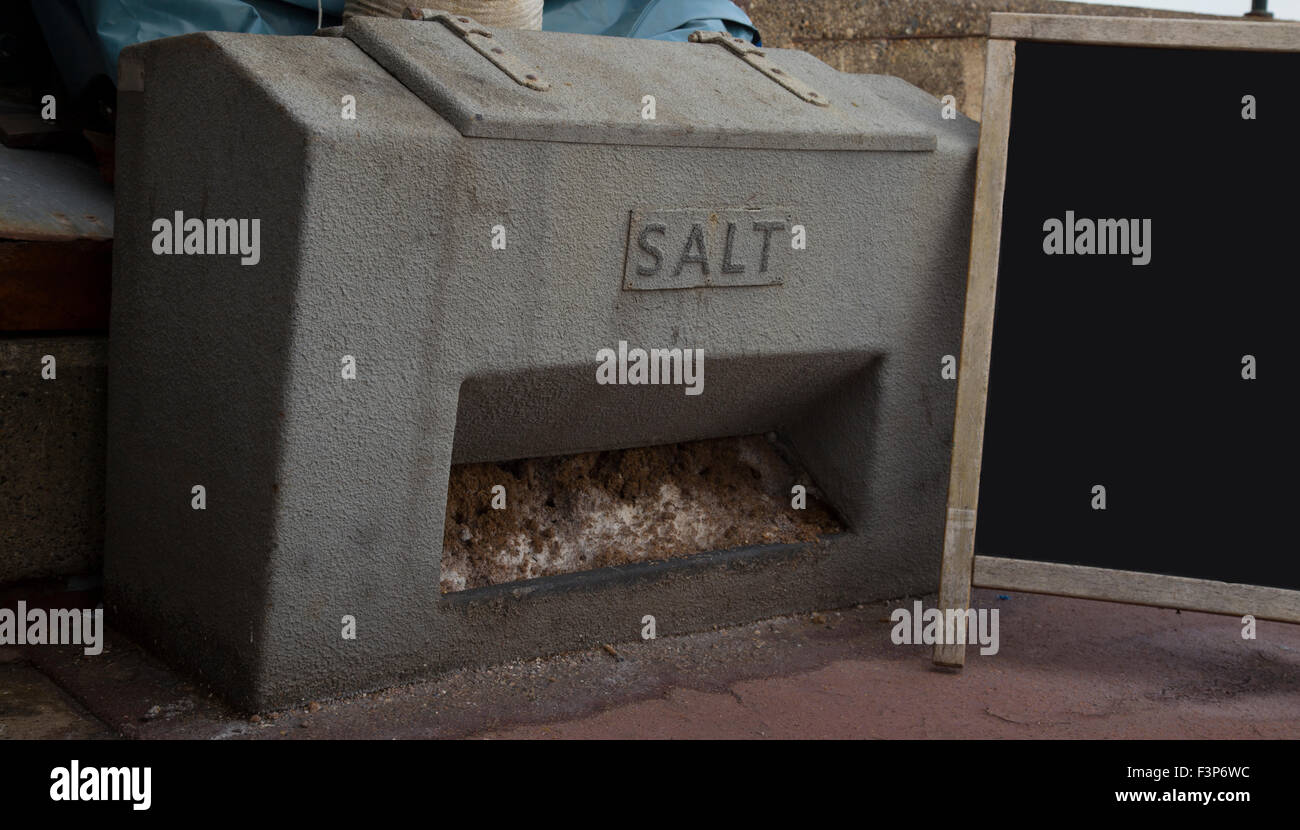 Large metal salt bin, with rock salt and a clear black board - Stock Image