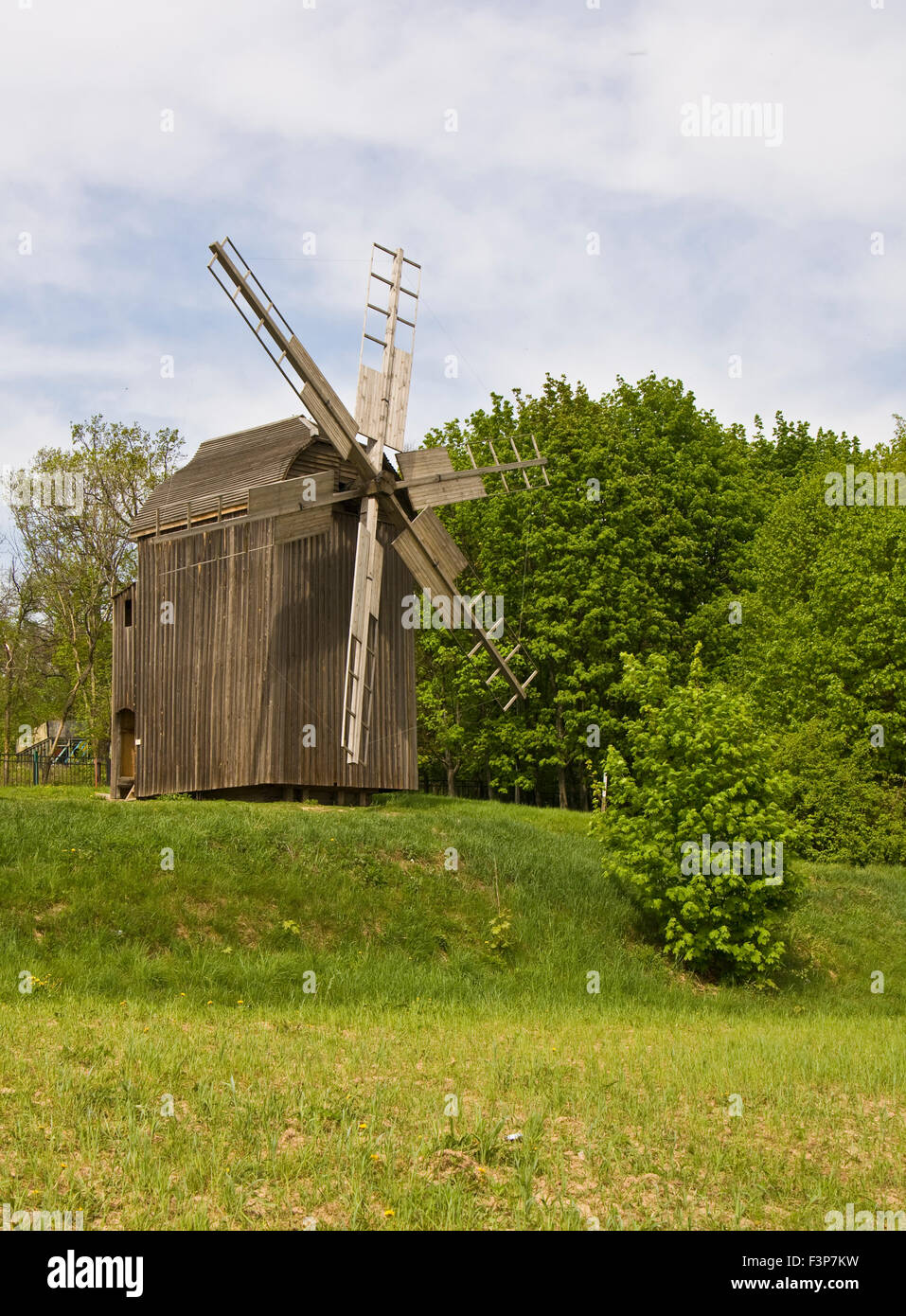 Wooden windmill in landscape. Recorded in outdoors museum of national architecture in Pirogovo near Kiev in Ukraine. - Stock Image