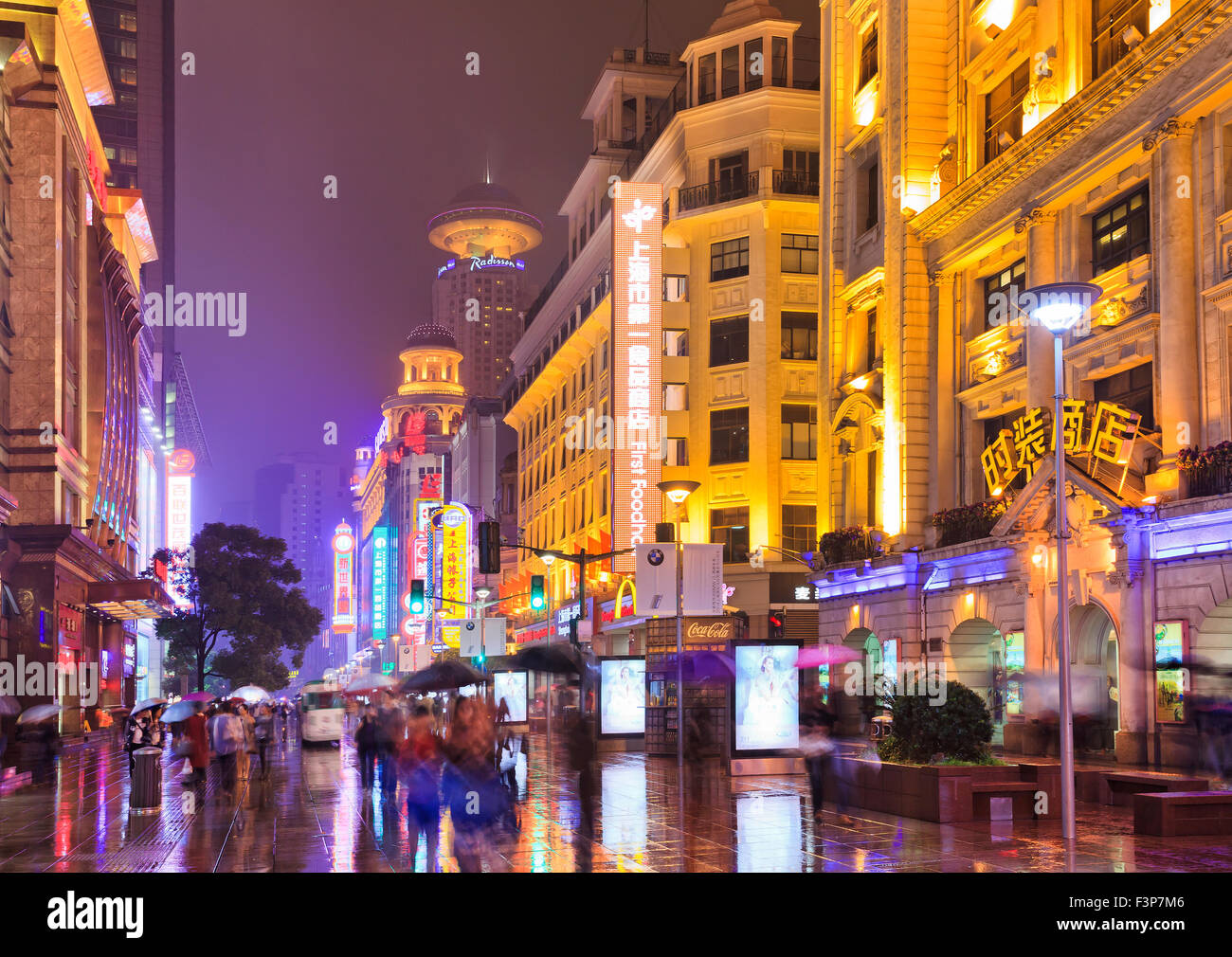 pedestrian walking shopping Nanking road street in Shanghai, China, at night with brightly lit by neon illimination - Stock Image