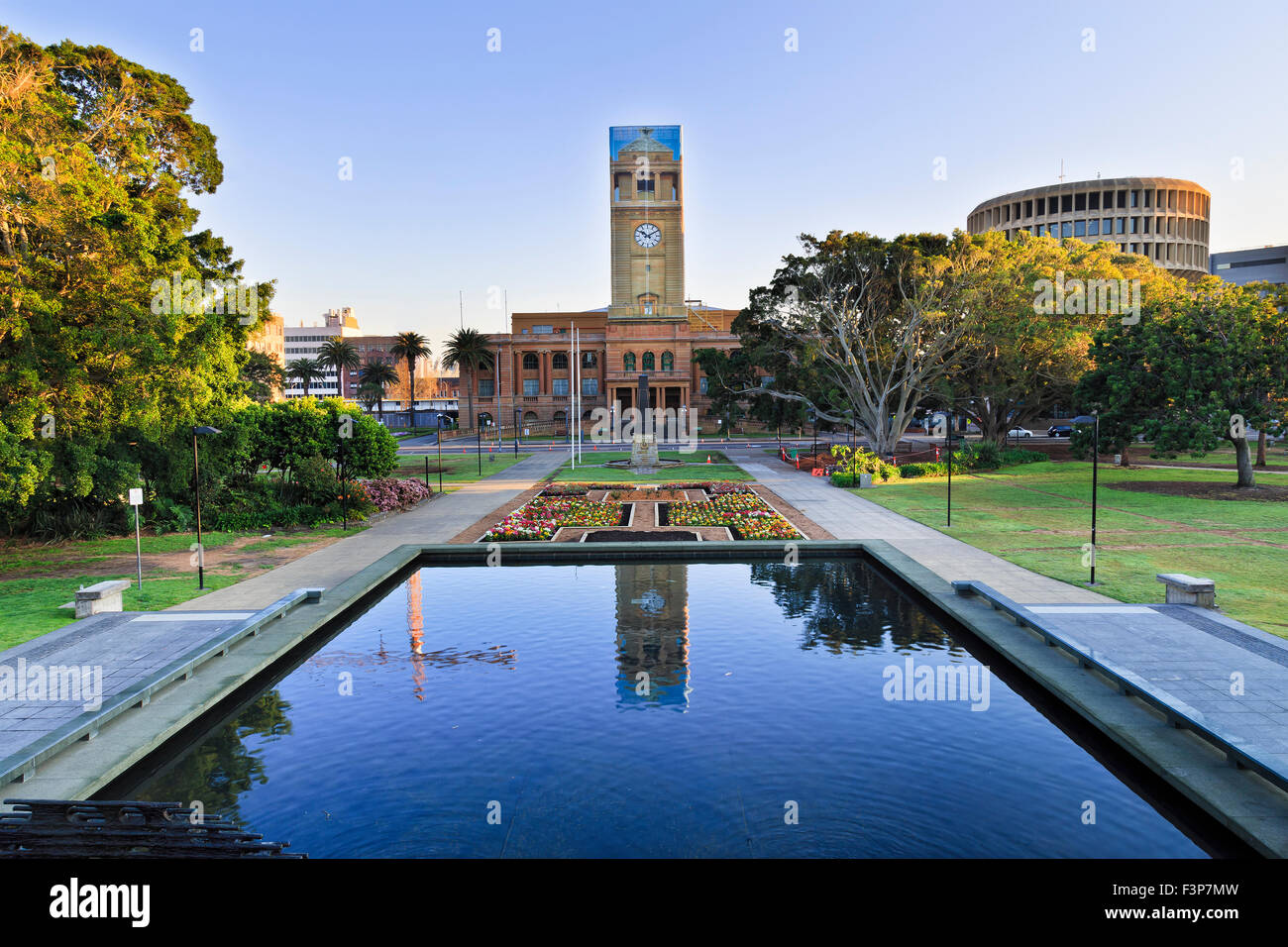 townhall of the city of Newcastle behind still pool in a park decorated by blooming flowers at sunrise - Stock Image