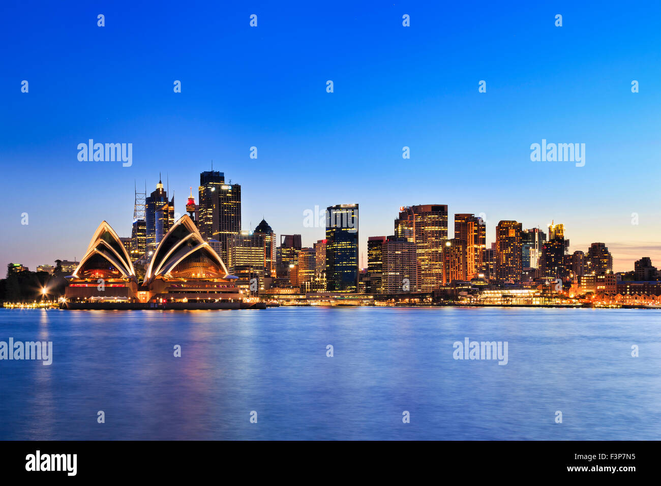 Sydney city landmarks around harbour at synset with illumination reflecting in blurred waters - Stock Image
