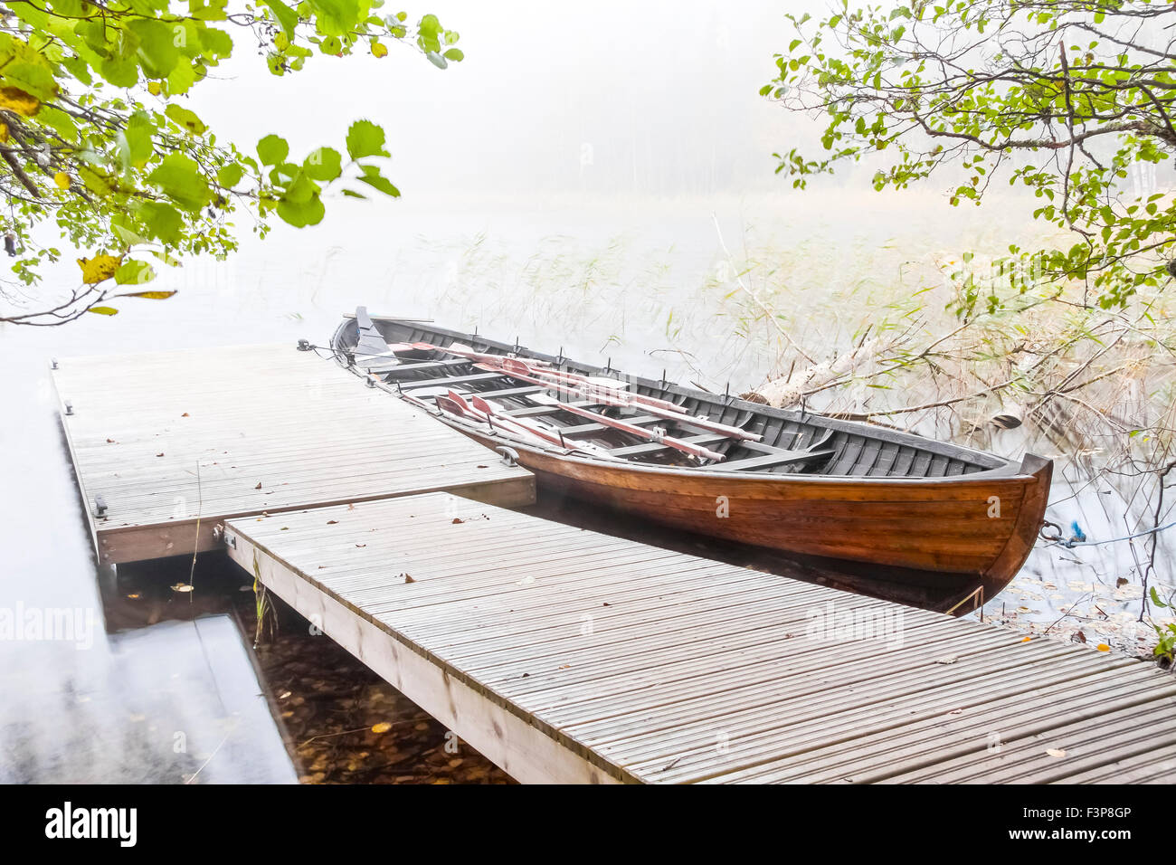 Long wood oar boat parked next to floating quay in a mist - Stock Image