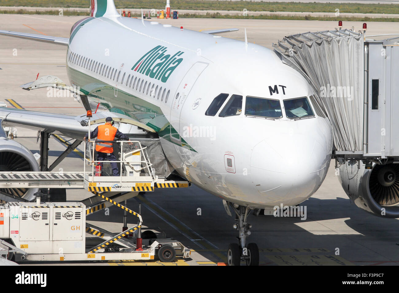 Alitalia, Passenger plane on the ground at at Linate airport, Milan, Italy. Ground crew are approaching the plane - Stock Image