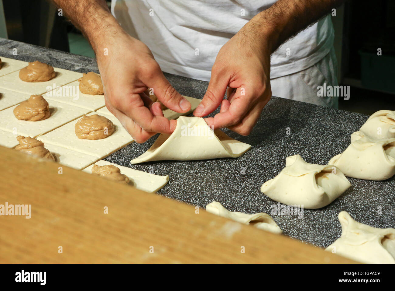 Baker working in a bakery - Stock Image