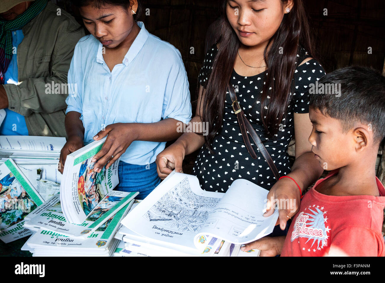 A curious boy looking at new textbooks in Cambodia, Asia. - Stock Image