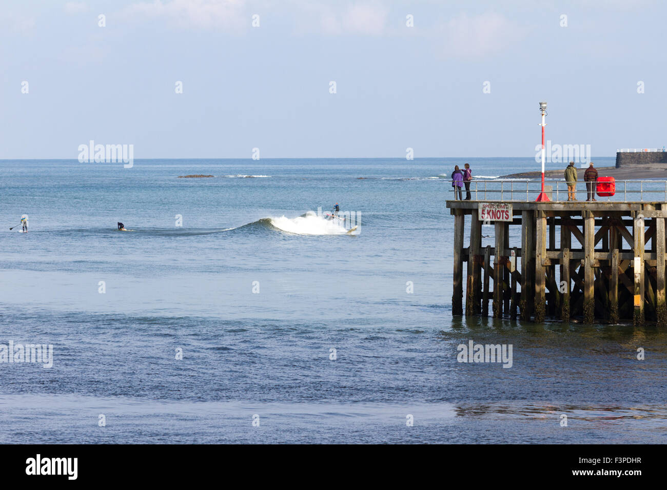surfers riding the waves on the coast of Aberystwyth - Stock Image
