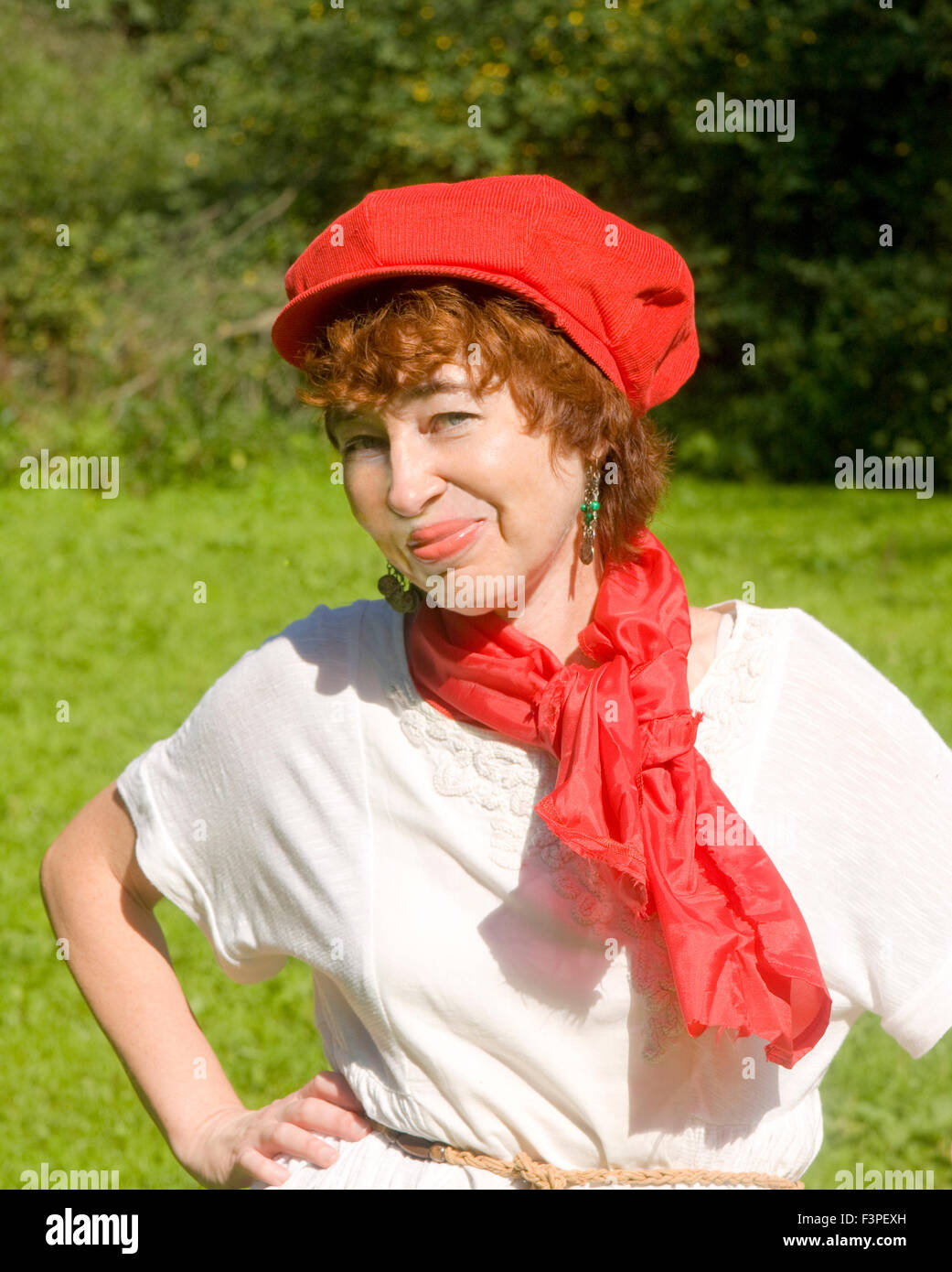 European woman in red hat smiling half body. - Stock Image