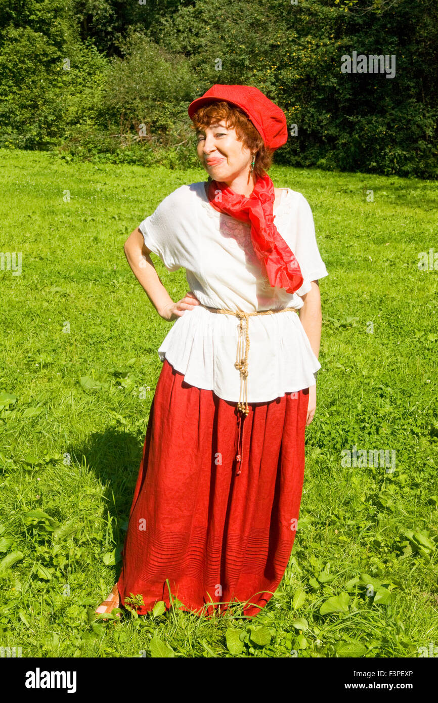 230d8319f European woman in red hat, white blouse and red skirt with red scarf  standing on grass meadow in park, forest behind.