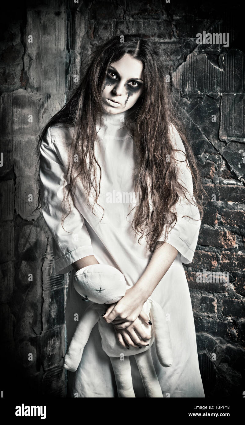Horror scene: the strange mysterious girl with moppet doll in hands - Stock Image