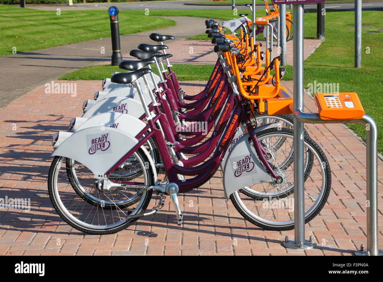 A row of ECO friendly Bikes for hire parked awaiting the commuters arrival to help keep things green and cars off - Stock Image