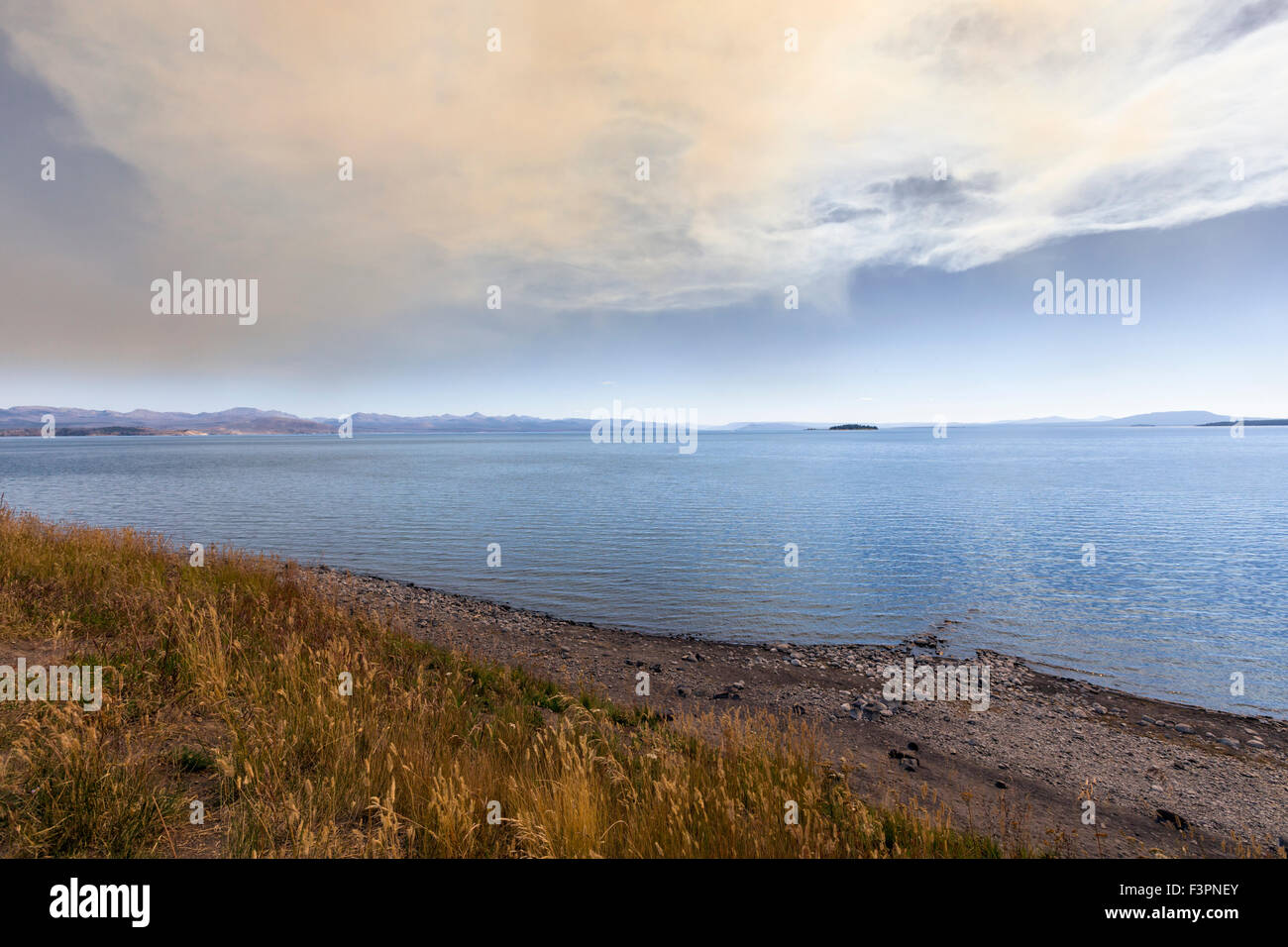 Smoke from a controlled forest fire over Yellowstone Lake; Yellowstone National Park; Wyoming; USA - Stock Image