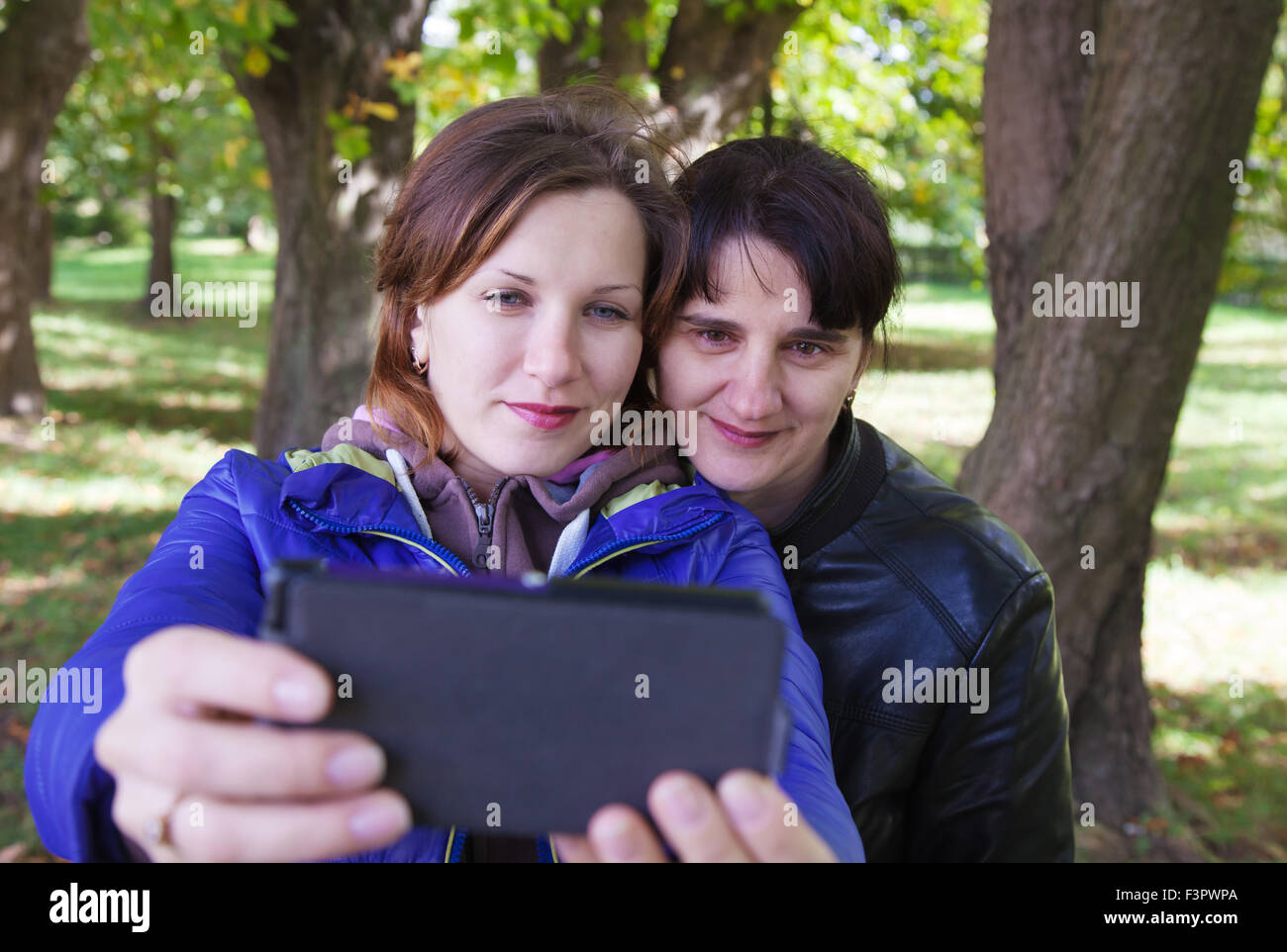 young woman with her mother taking pictures of themselves a mobile phone on autumn day outside Stock Photo