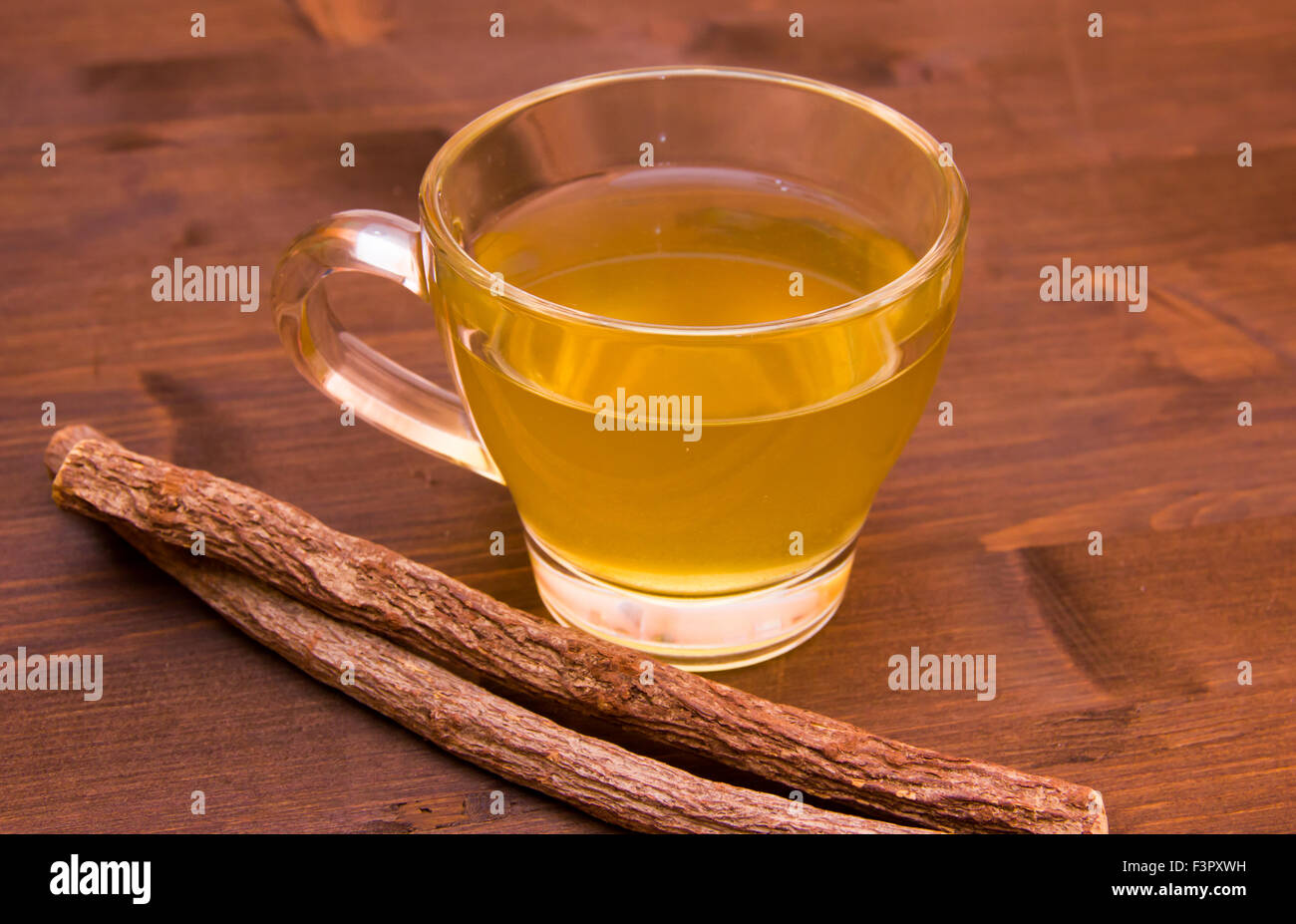 Cup of herbal tea licorice in wooden table - Stock Image