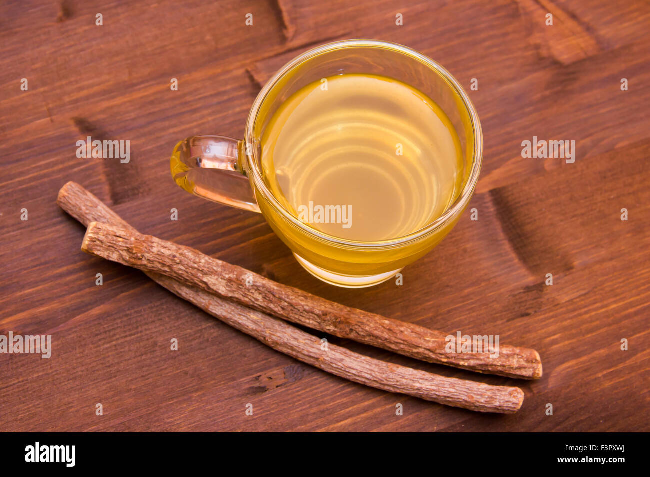 Cup of herbal tea licorice in wooden table top view - Stock Image