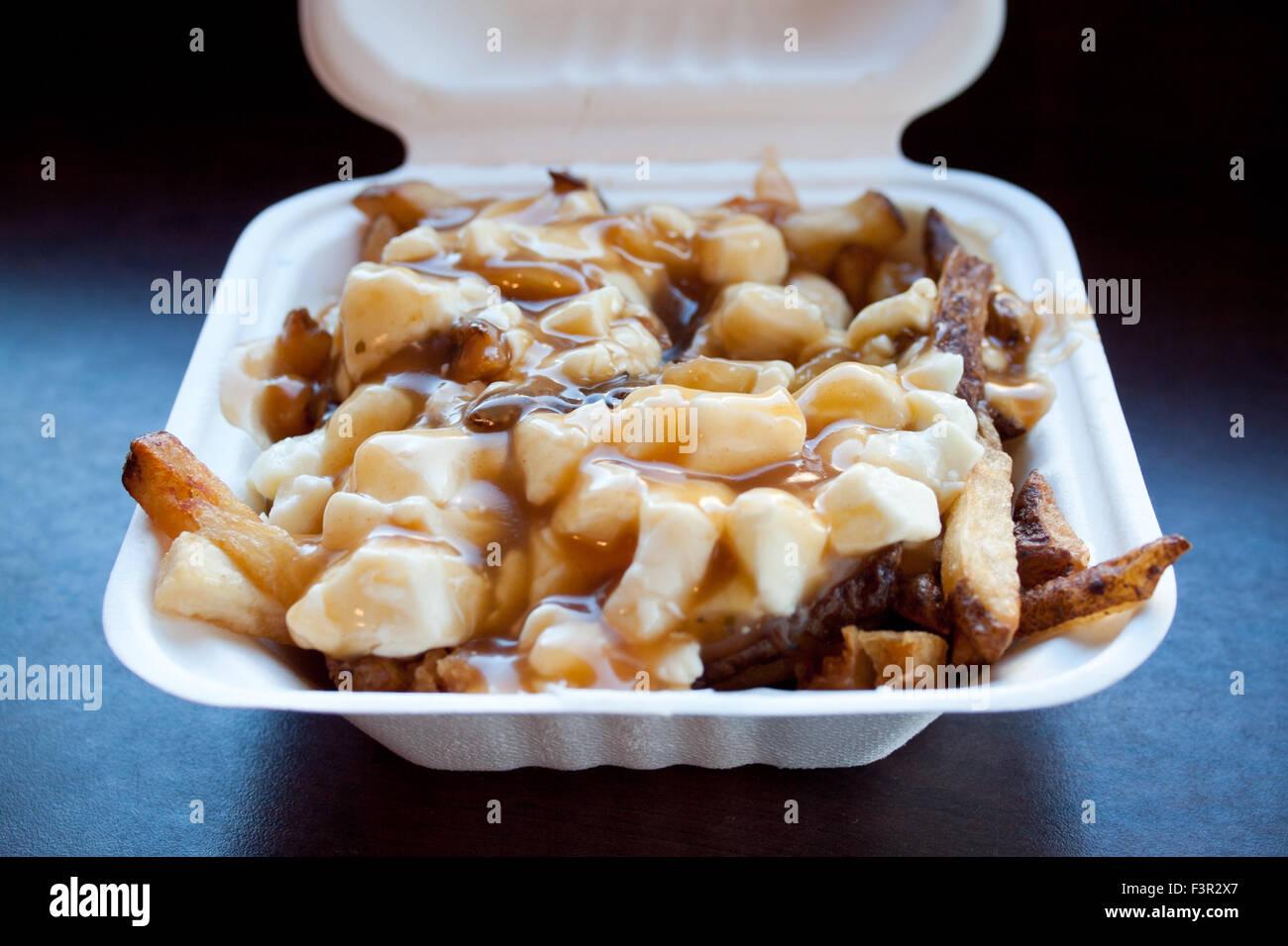 A takeout box of classic Quebec poutine from La Poutine in Edmonton, Alberta, Canada. - Stock Image