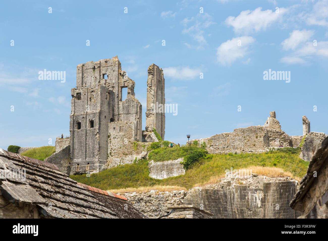 Iconic ruins of hilltop medieval Corfe Castle, a popular leading sightseeing landmark in Wessex, Dorset, southwest - Stock Image