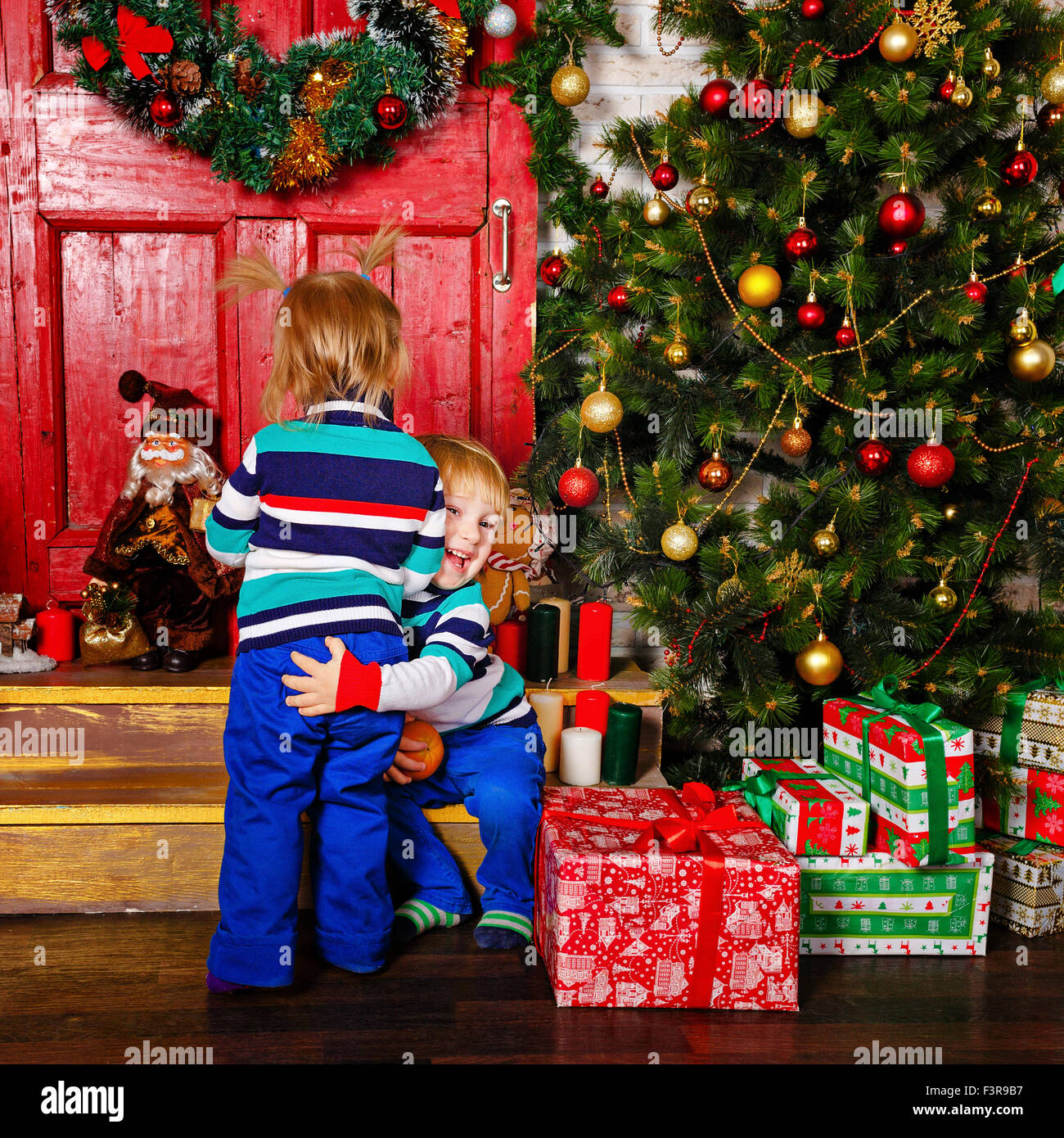 Merry Christmas Brother.Brother Hugging His Sister Near A Christmas Tree Cute