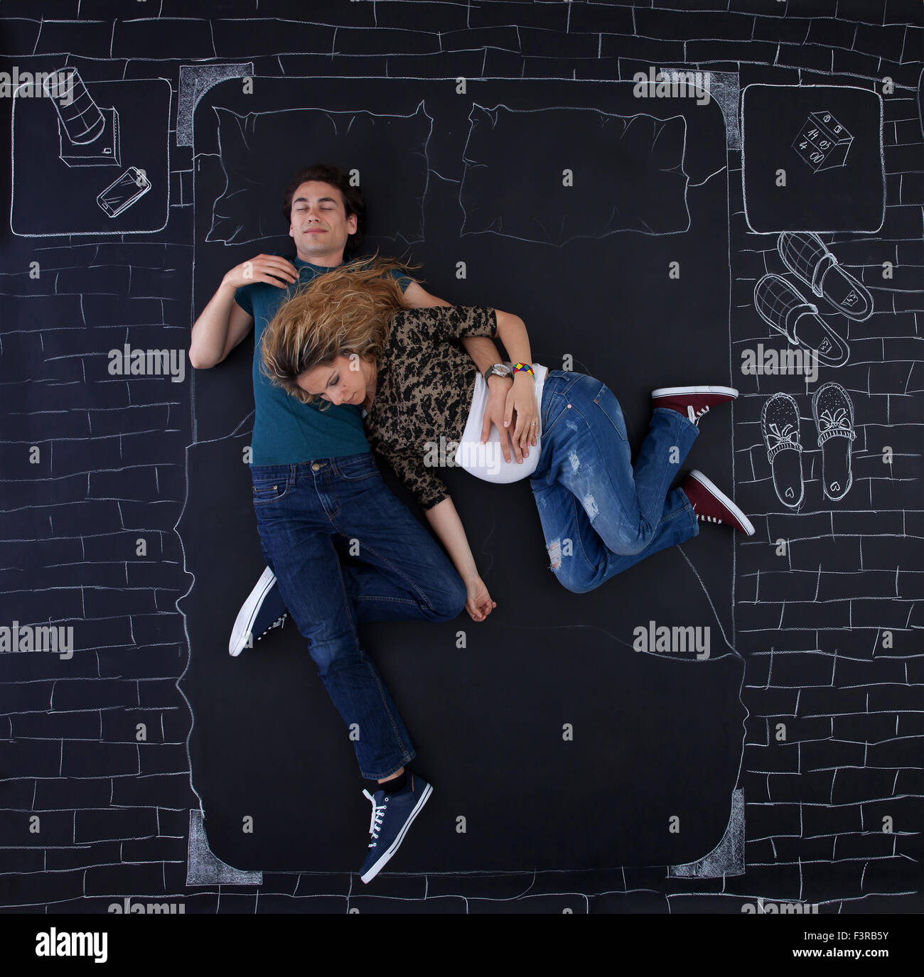 Young couple sleeping in bed in funny positions. - Stock Image