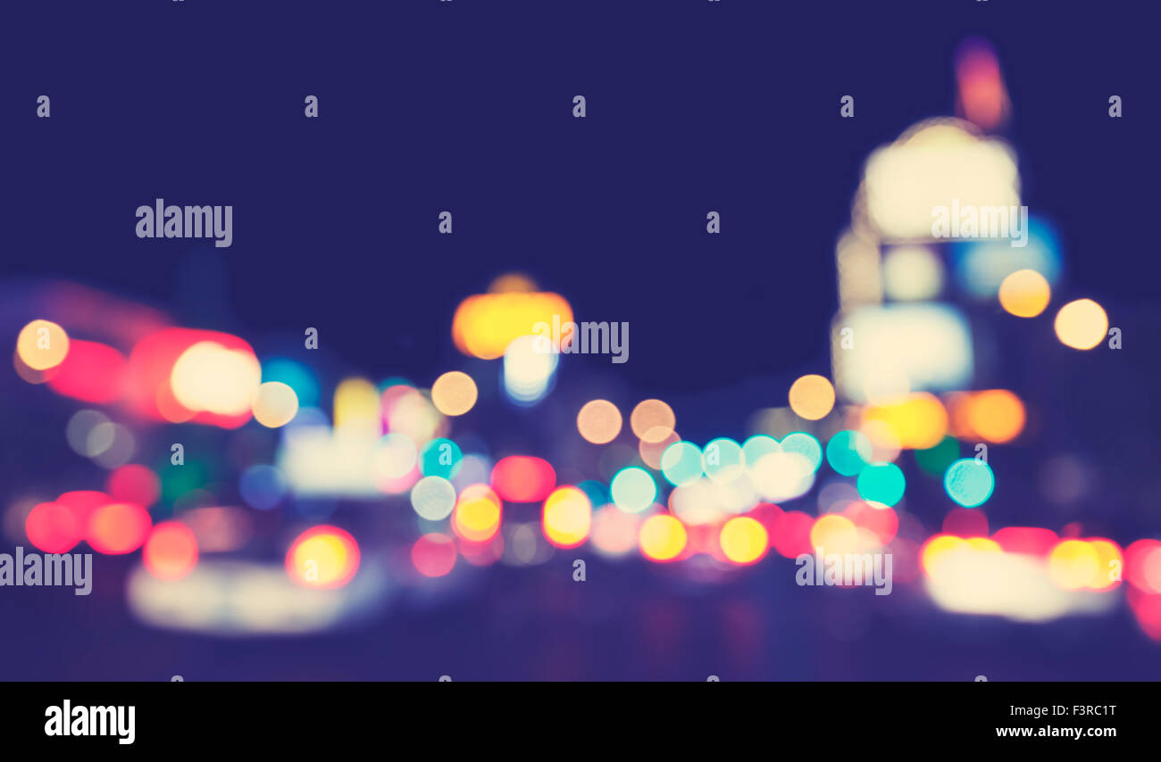 Vintage toned blurred city lights at night, urban abstract background. - Stock Image