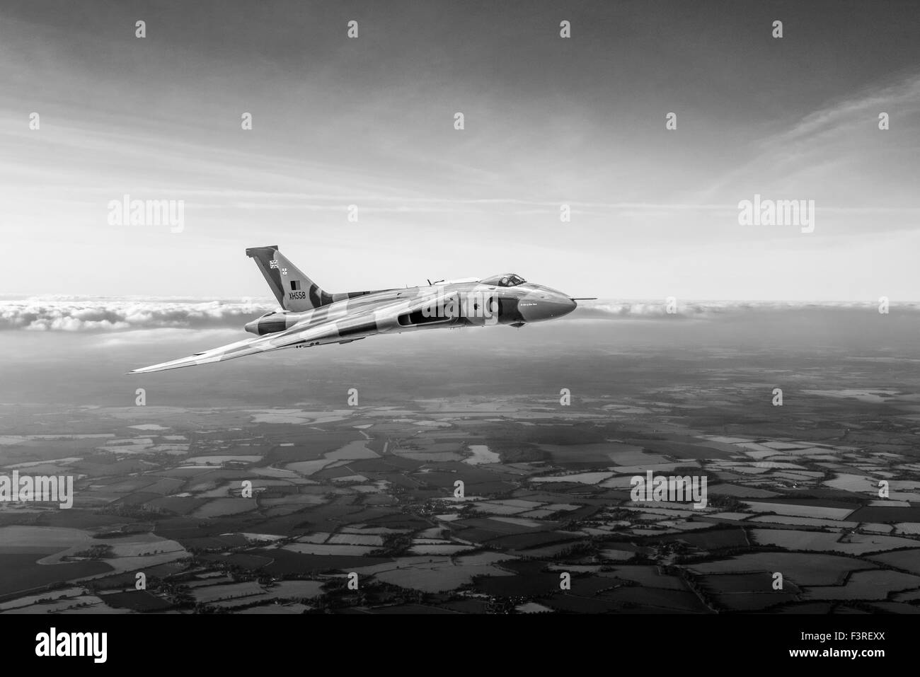 A depiction of an Avro Vulcan delta wing strategic bomber in the skies over the British countryside. Black and white - Stock Image