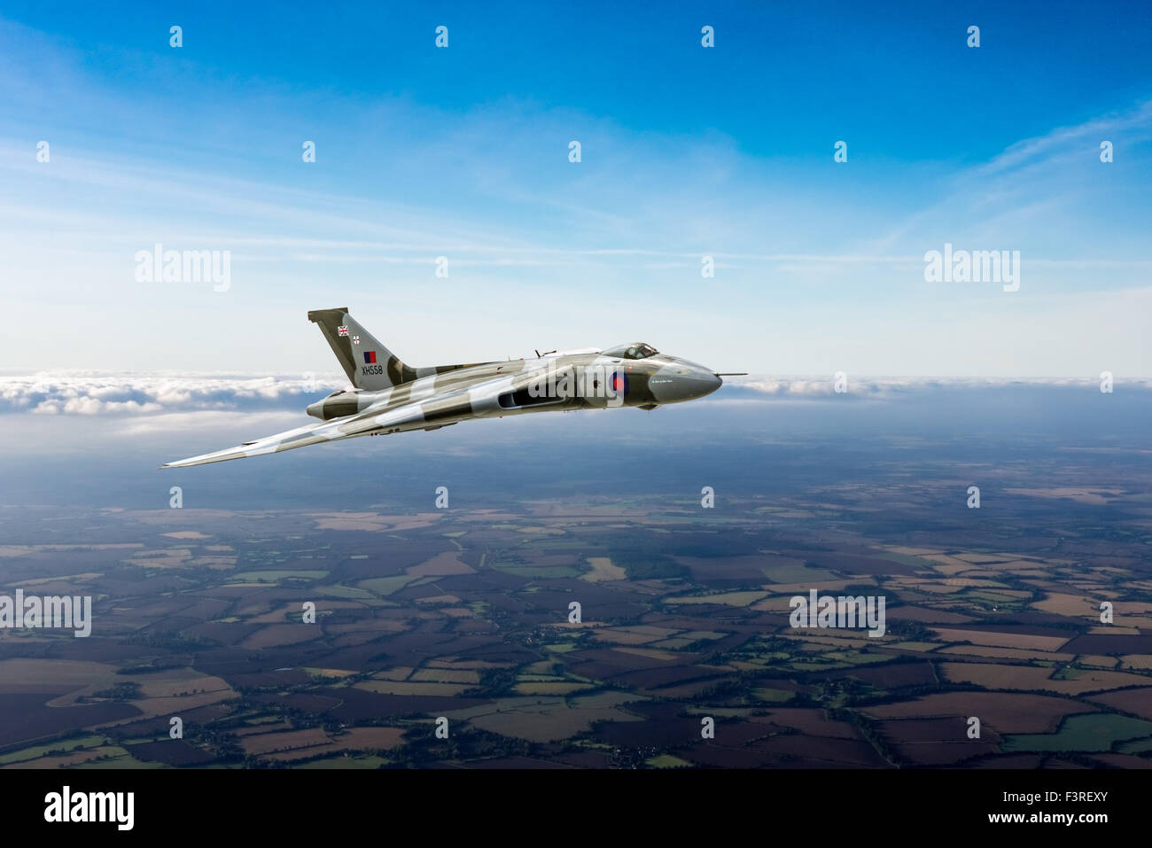 A depiction of an Avro Vulcan delta wing strategic bomber in the skies over the British countryside. - Stock Image