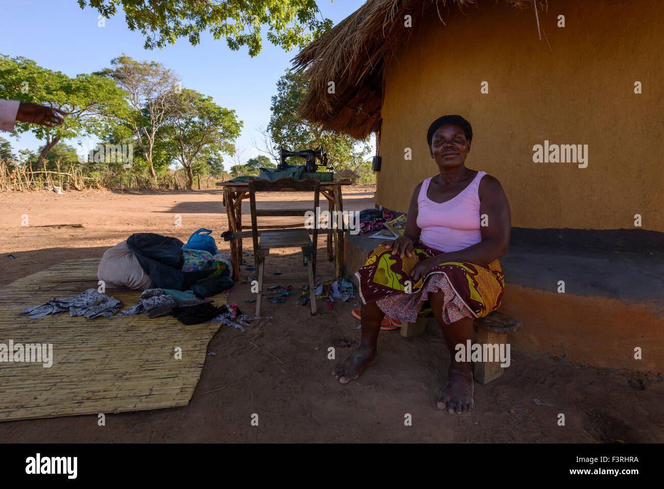 Seamstress sitting in front of a house, Zambia, Africa - Stock Image