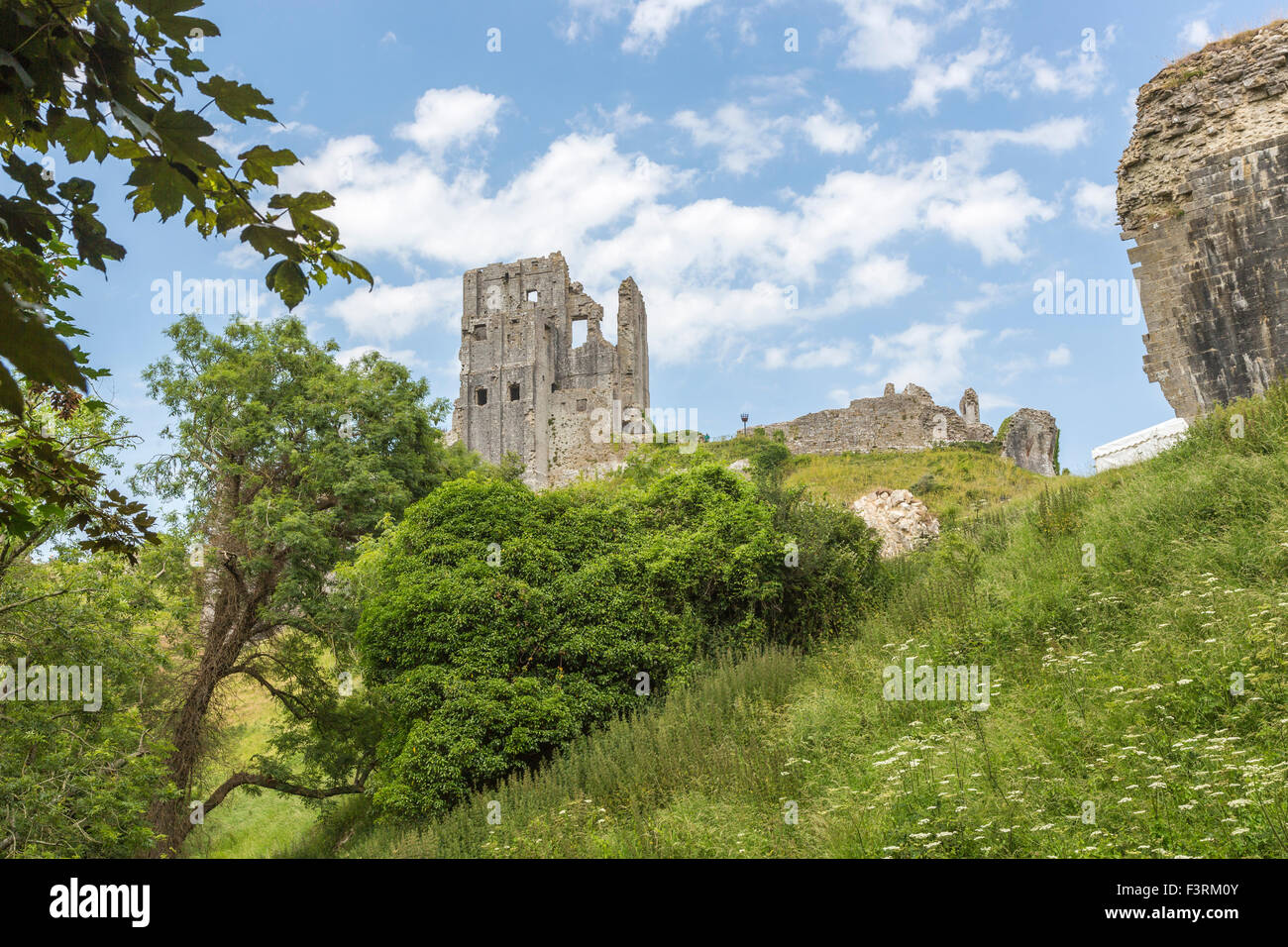 The hilltop ruins of Corfe Castle in Corfe, Dorset, south-west England on a sunny day with blue sky - Stock Image