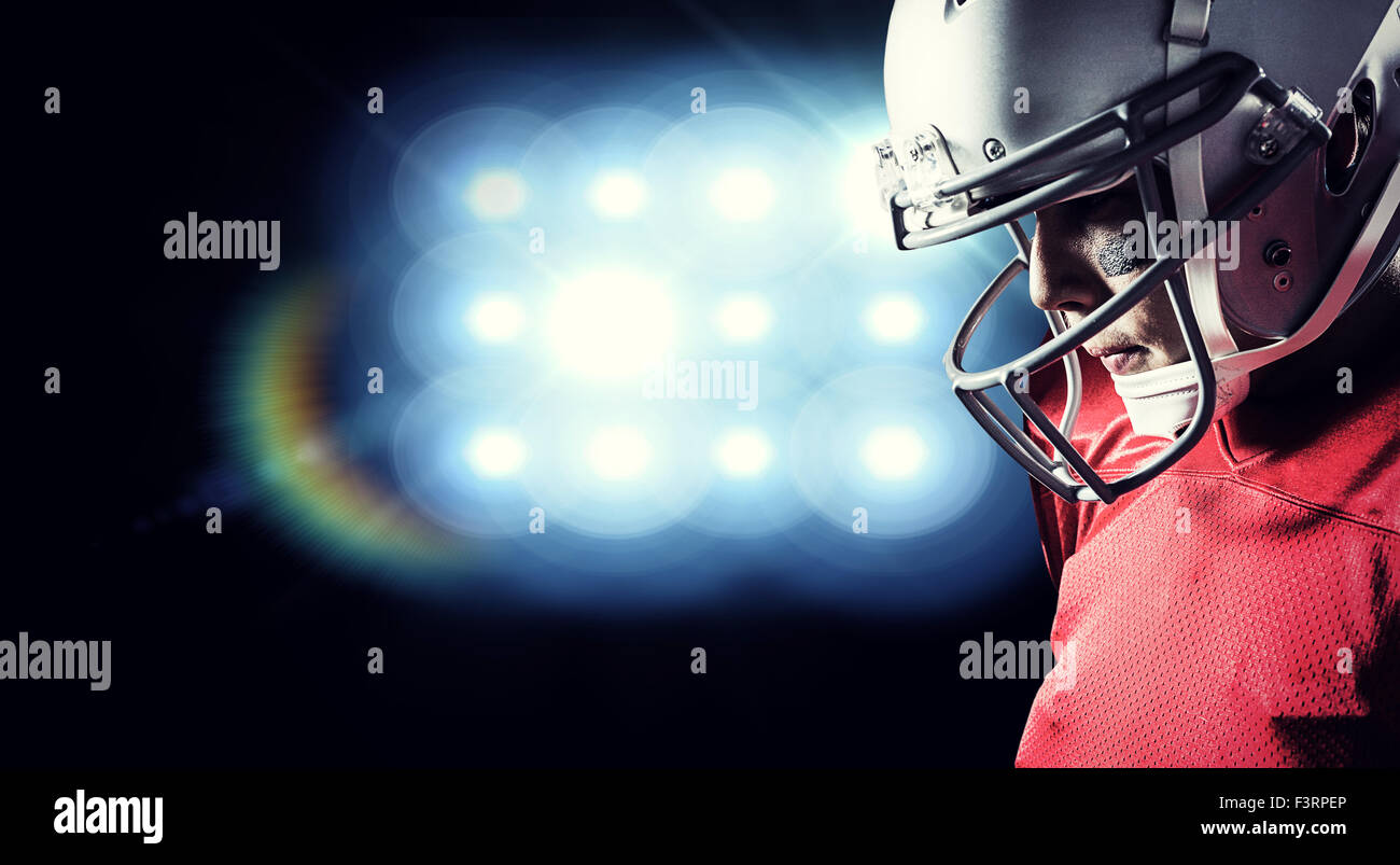 Composite image of american footballer looking down - Stock Image