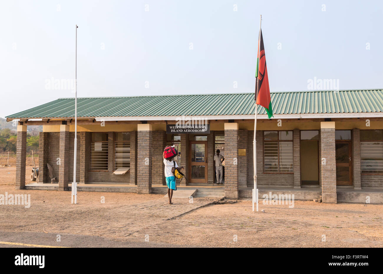 Air transport and travel, flying in Malawi: porter carrying luggage, Likoma Island Aerodrome terminal building, - Stock Image