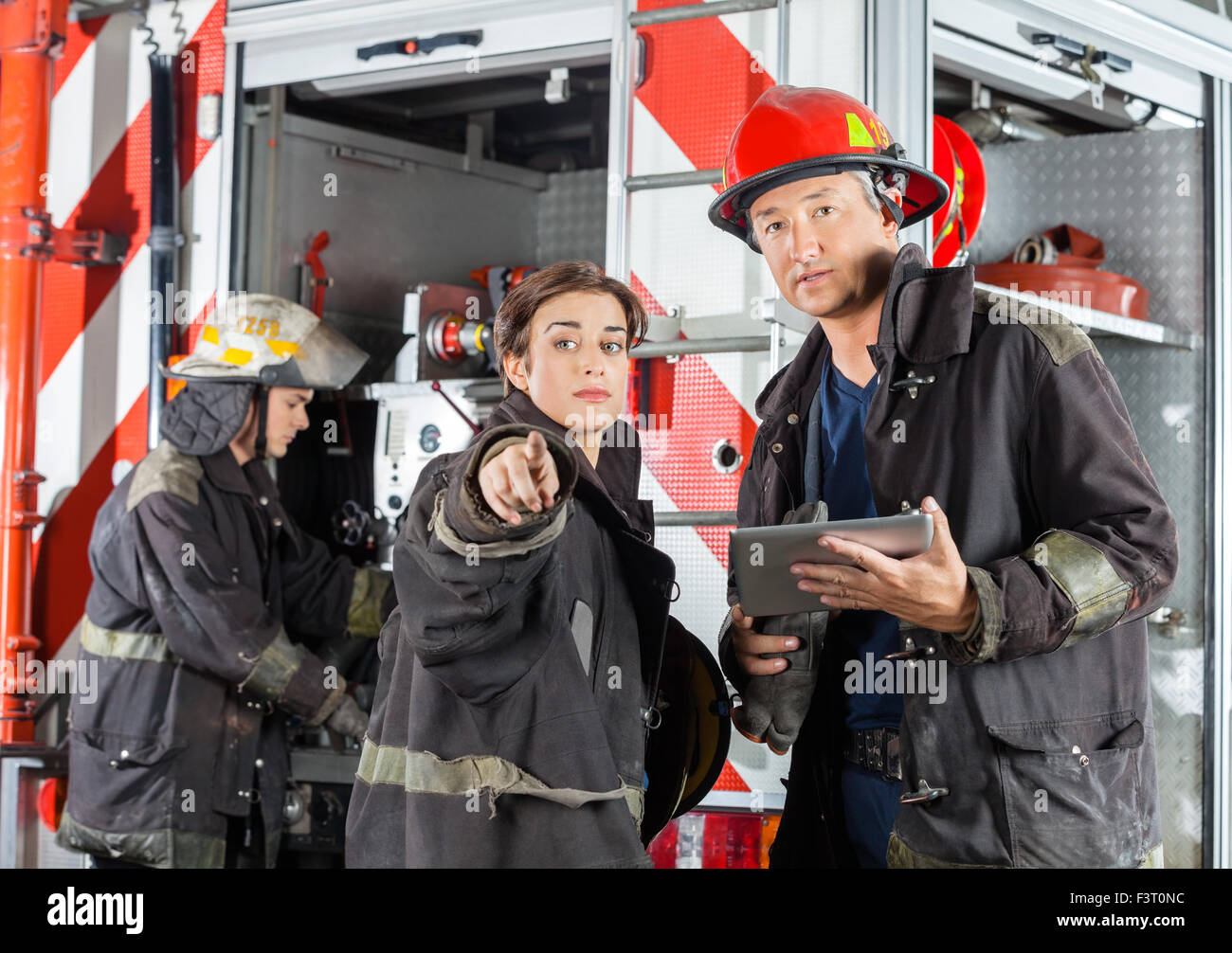 Firefighter Showing Something To Colleague At Fire Station - Stock Image
