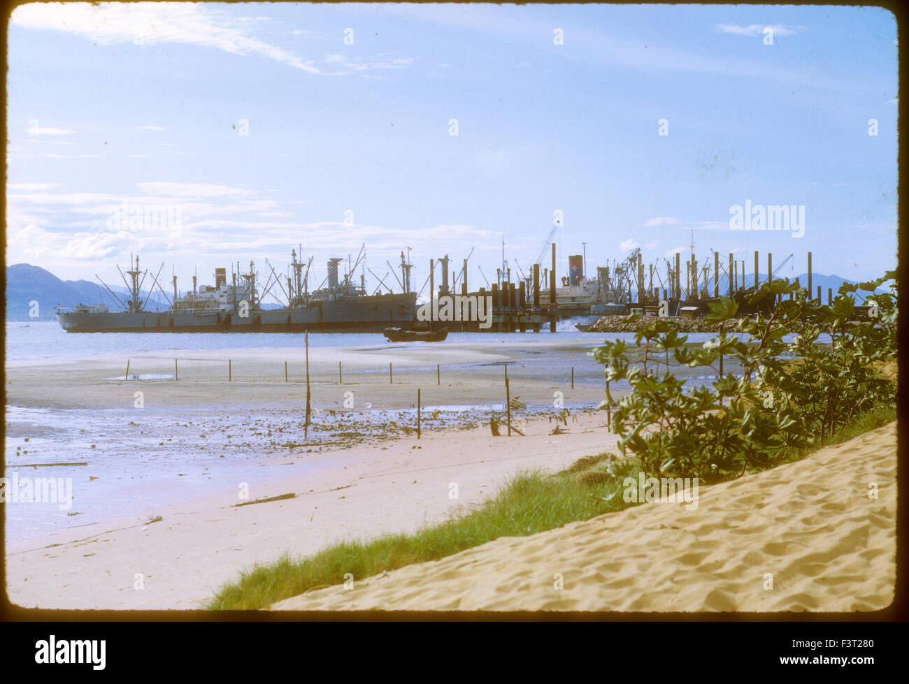 United States Navy ships line up in Cam Rahn Bay harbor where many supplies for the war arrived in South Vietnam - Stock Image