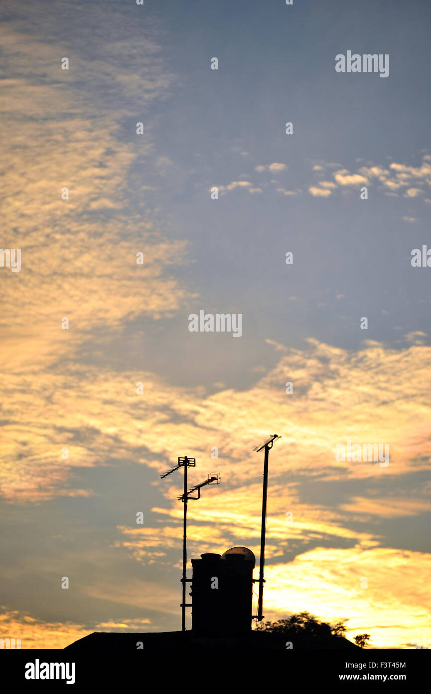118ea60d6b The roof of a house with a chimney and TV aerials silhouetted against a  dramatic sunset