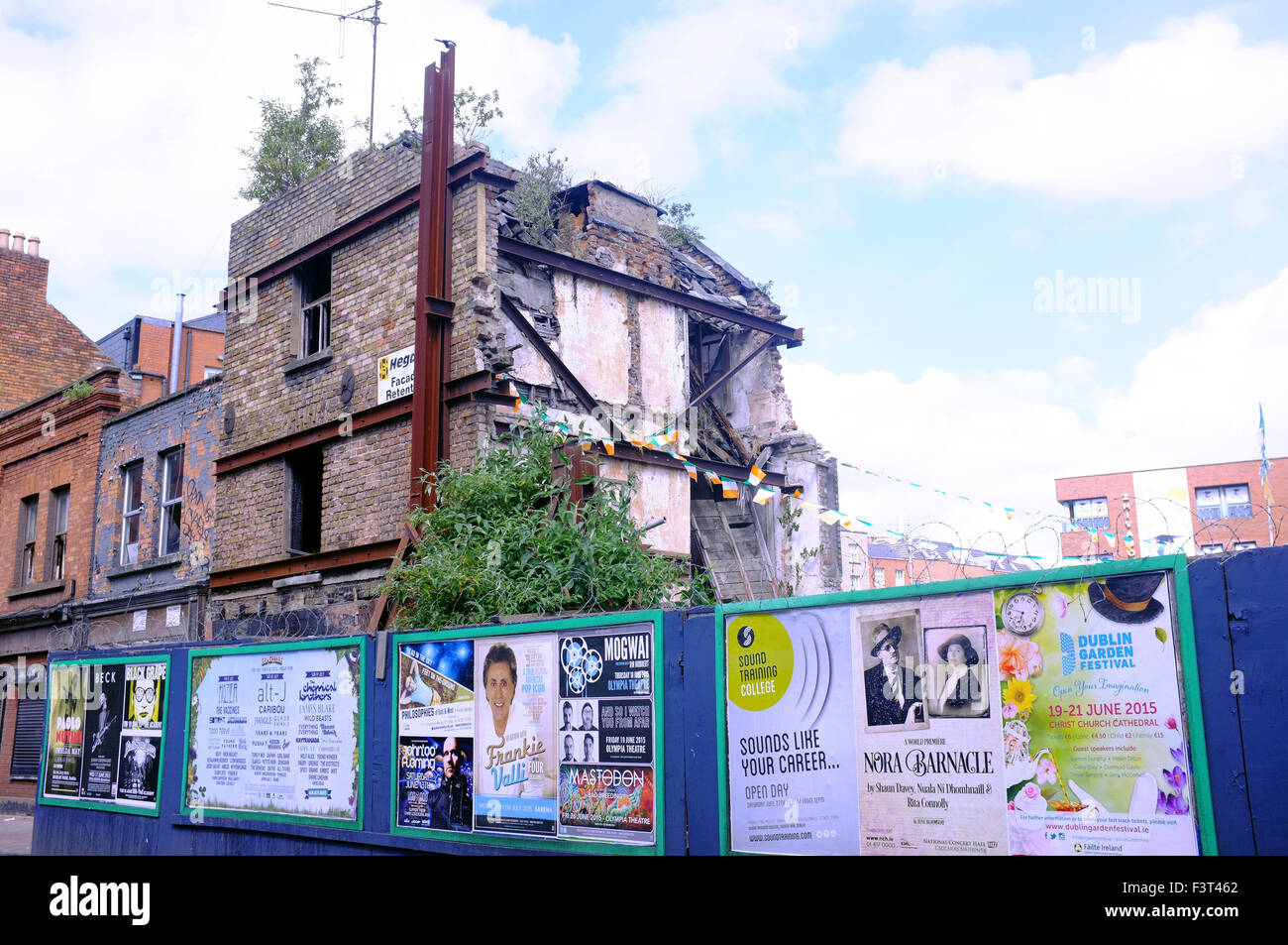 A half demolished building surrounded by fencing in Dublin. - Stock Image