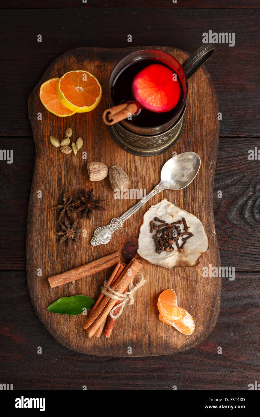 Glass of mulled wine (punch) in glass-holder served on wooden plate with spices over dark wooden table. Top view Stock Photo