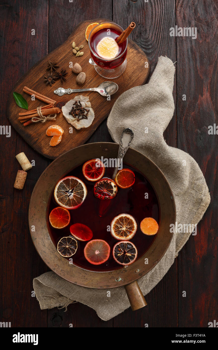 Brass bowl full of mulled wine (punch) next to glass of mulled wine served on wooden plate with spices over dark - Stock Image