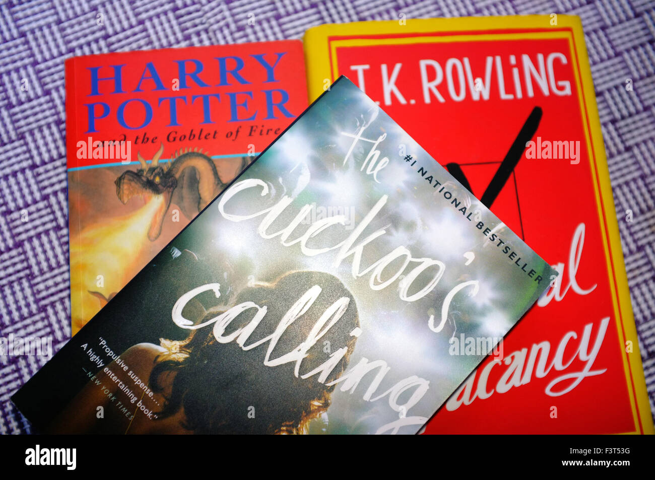 The J.K. Rowling books Harry Potter, The Casual Vacancy and The Cuckoo's Calling photographed against a purple - Stock Image