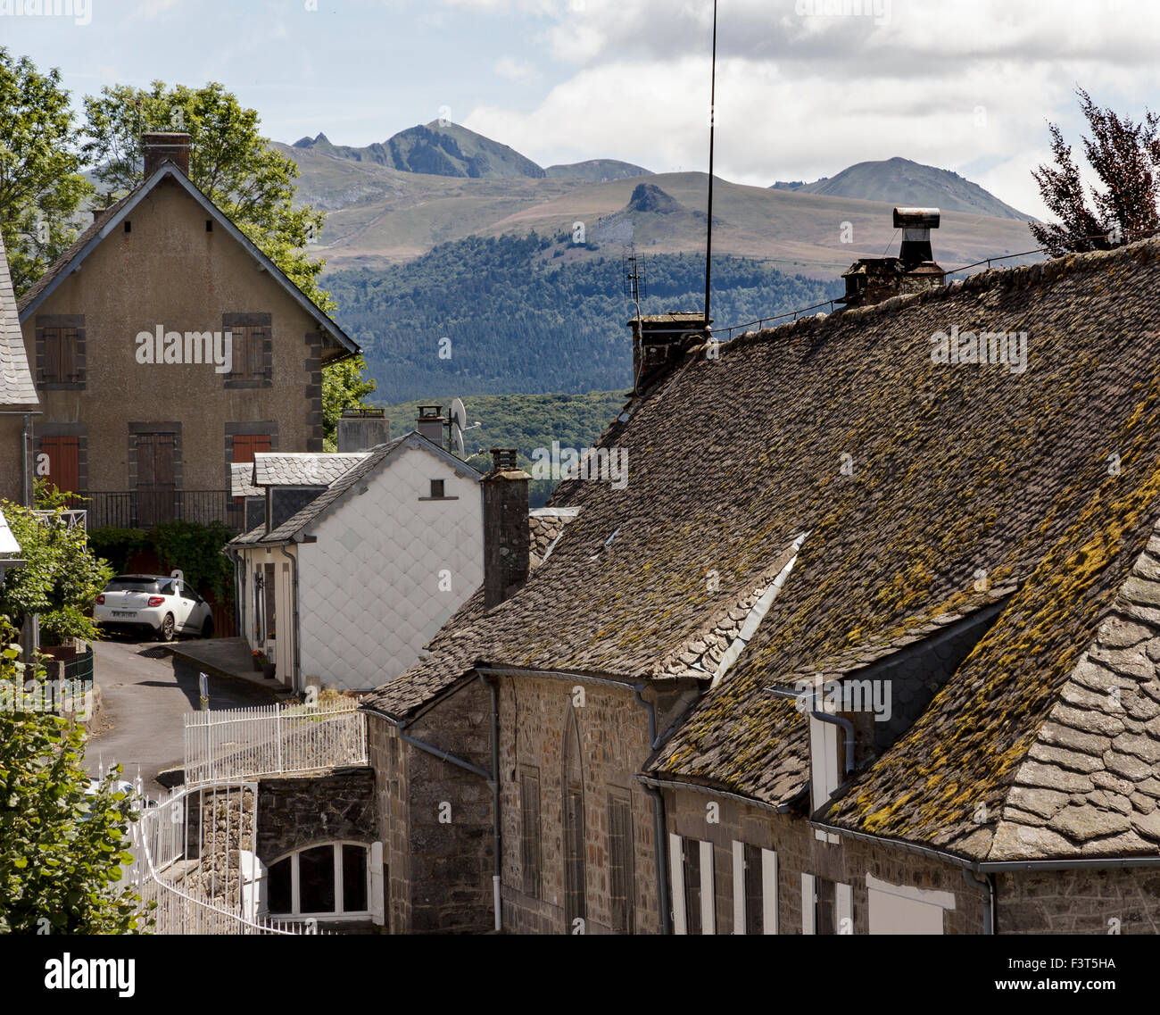 The town of La Tour d'Auvergne with Puy de Sancy and another extinct volcano in the background - Stock Image