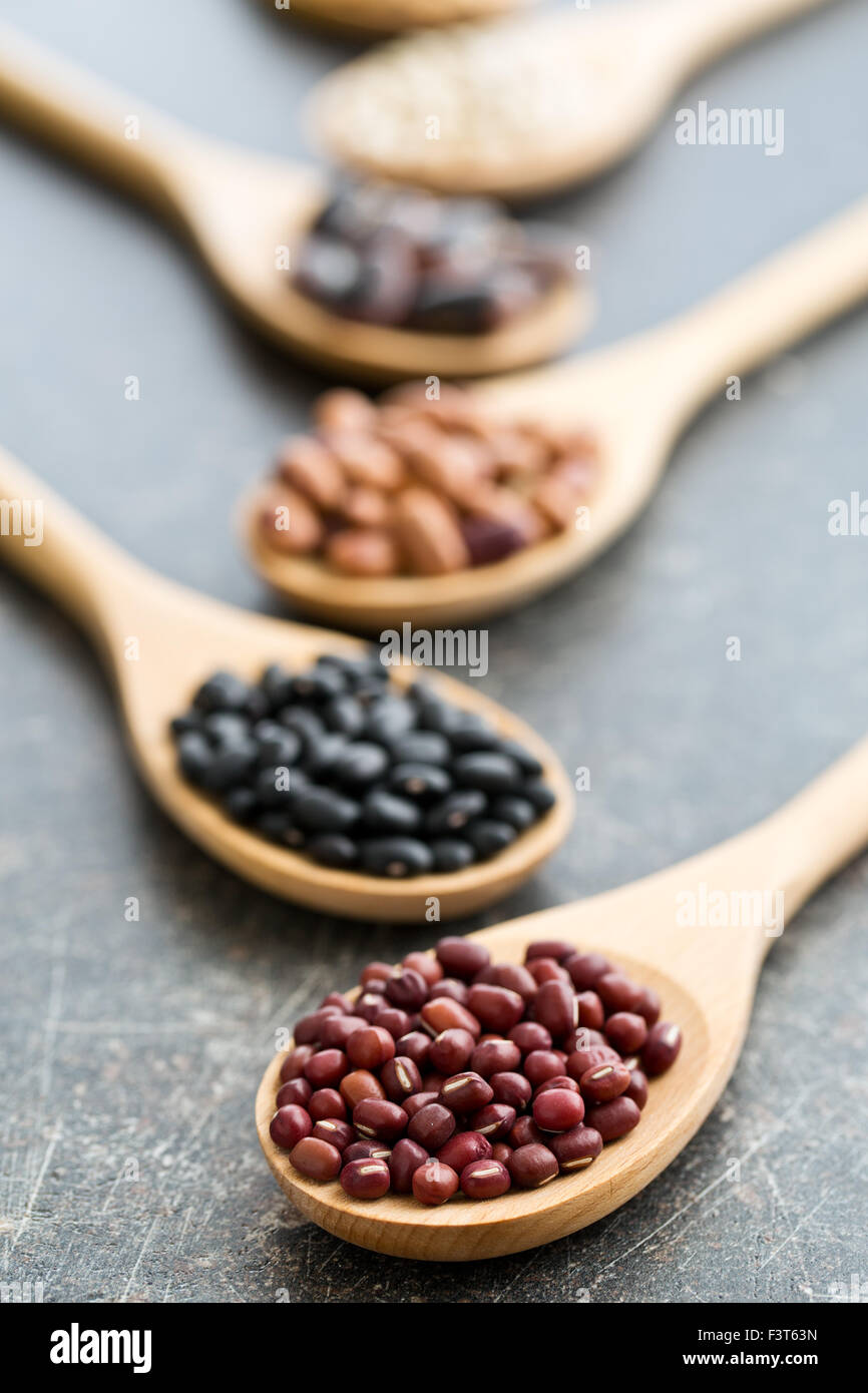 various uncooked legumes in wooden spoons - Stock Image