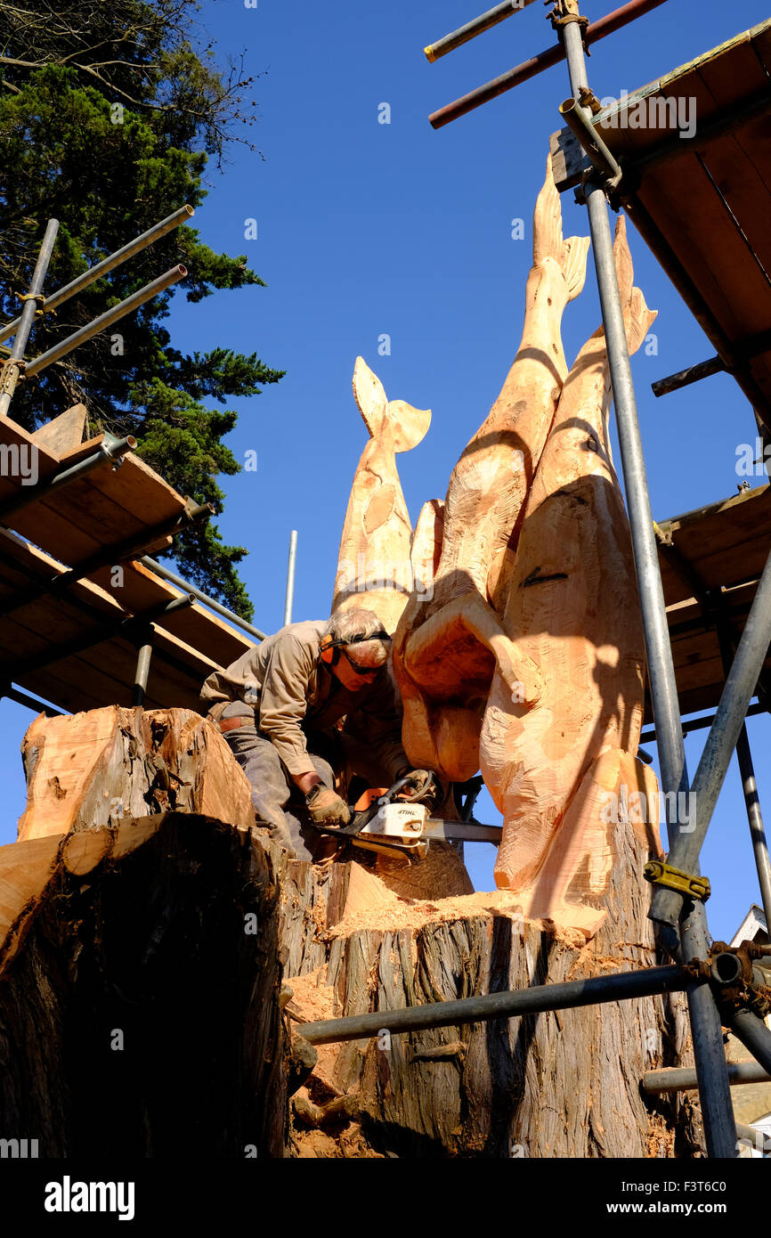 Paul Sivell wood carver sculpture sculptor artist artisan man carving mermaids and dolphins out of tree stump outside - Stock Image