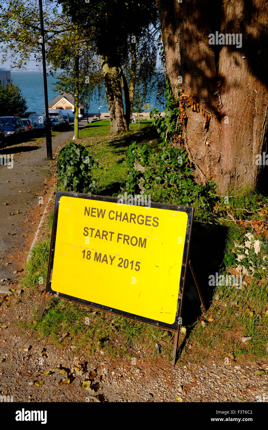 Road sign new charges start from 18 may 2015 warning increased parking car parked off road ticket park restricted Stock Photo
