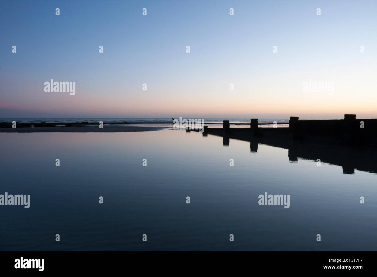 Reflections at dusk and lone figure on a tranquil beach, Bexhill on Sea, East Sussex, England, UK - Stock Image