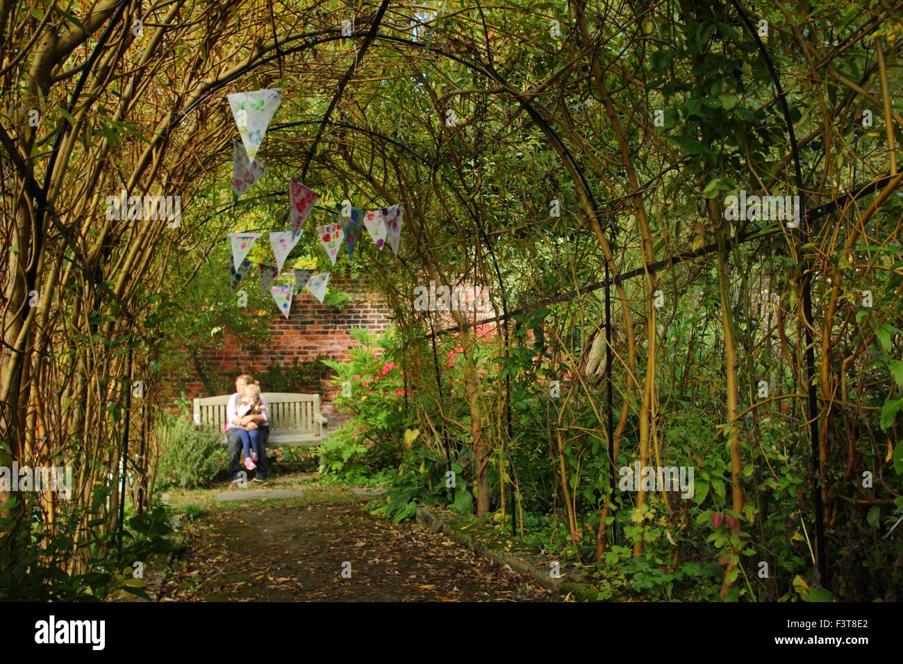 A Willow Arch Fashioned As A Tunnel Frames A Garden Bench In A Walled Garden  Where