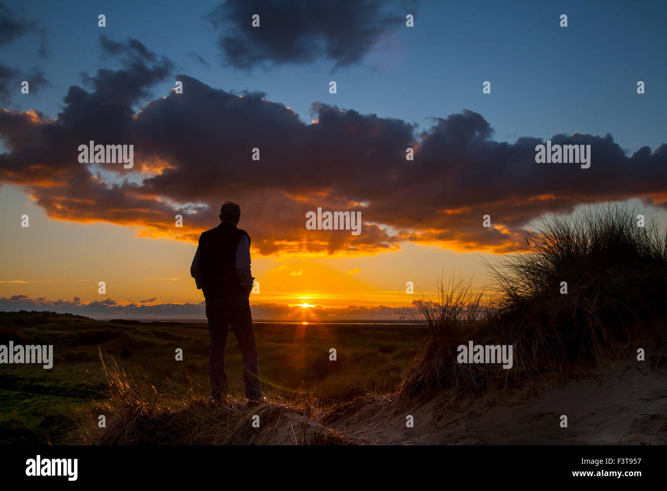Southport, Merseyside, UK 12th October, 2015. Silhouette man. UK Weather. Colourful sunset over the Irish Sea and Stock Photo
