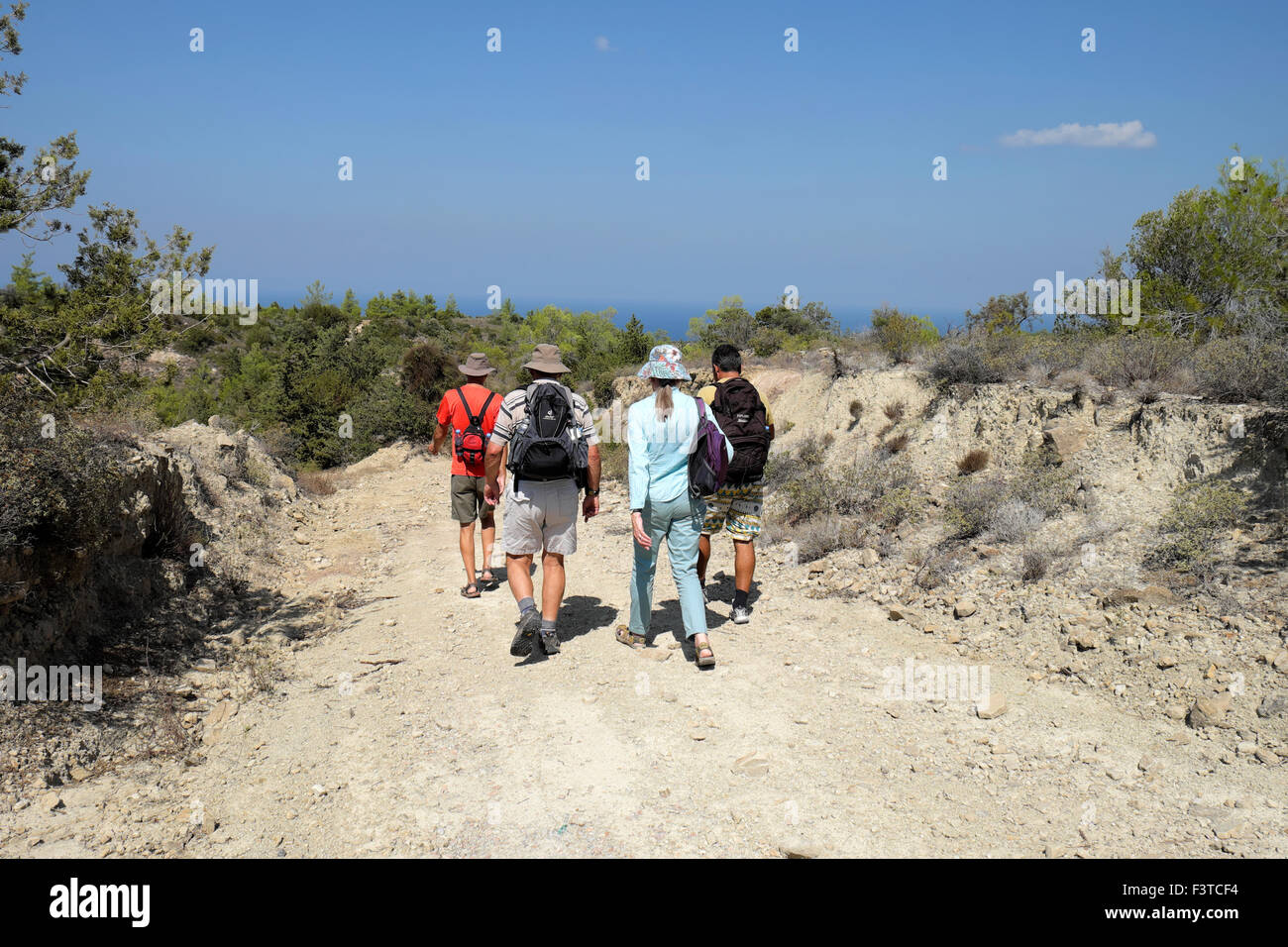 Walkers walking with backpacks on a path near the Kaplica Coast in North Cyprus  KATHY DEWITT - Stock Image