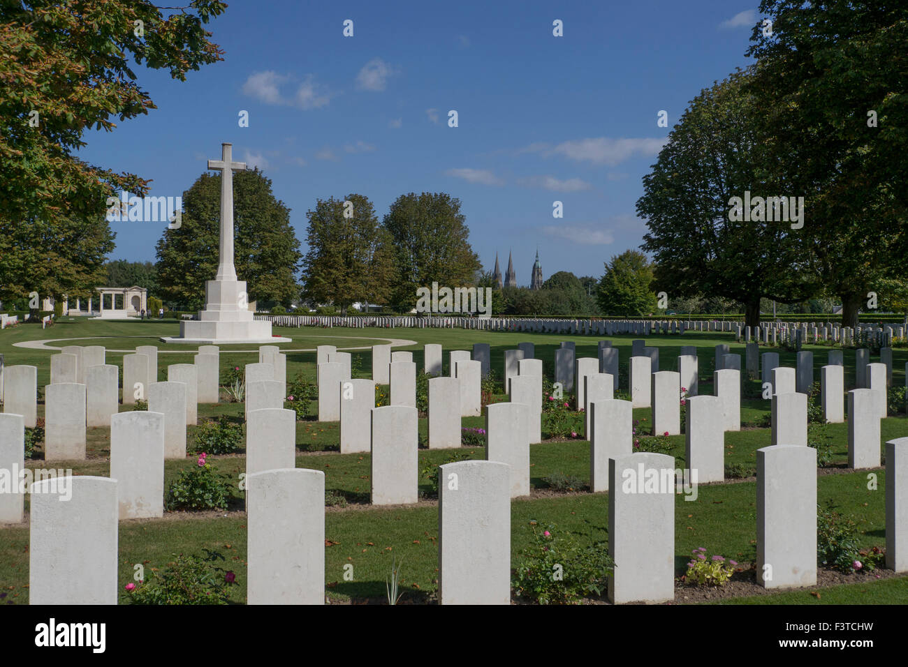 War Graves and Memorial Cross with Bayeux Catherdral in distance - Stock Image