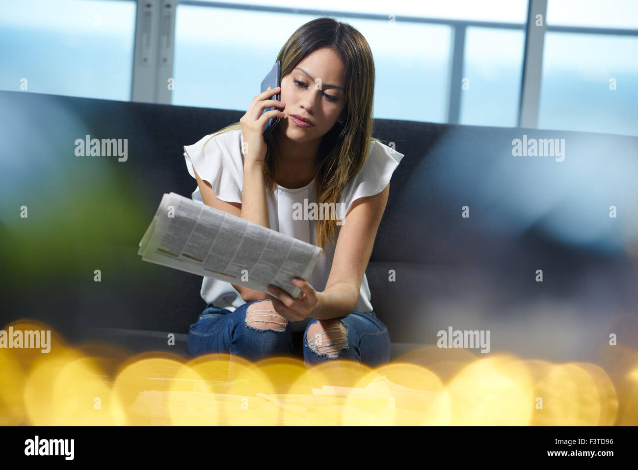 Young unemployed female doing job hunting and reading employment announcements. The girl is sitting on her sofa - Stock Image