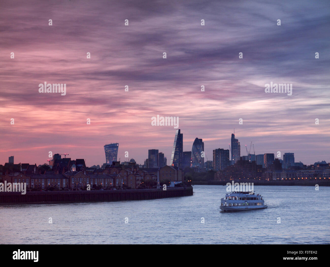 London financial city centre London viewed from Canary Wharf with river cruise boat in foreground at sunset London - Stock Image