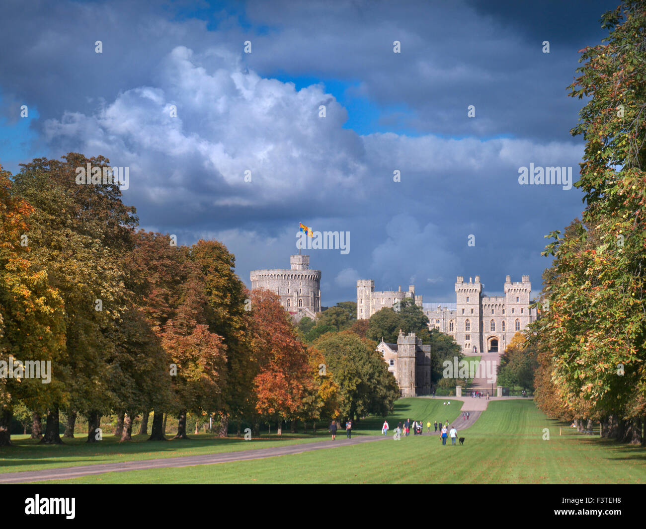 Windsor Castle flying Royal Standard viewed down the Long Walk with walkers, in autumnal colour with dramatic sky - Stock Image