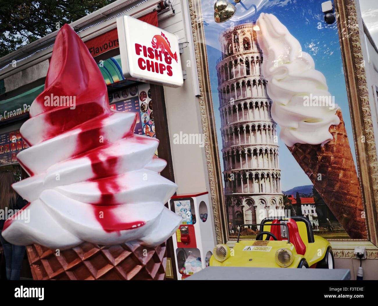 Contrasting point of sales display styles at kitsch tourist shop displaying fish & chips sign with ice cream - Stock Image