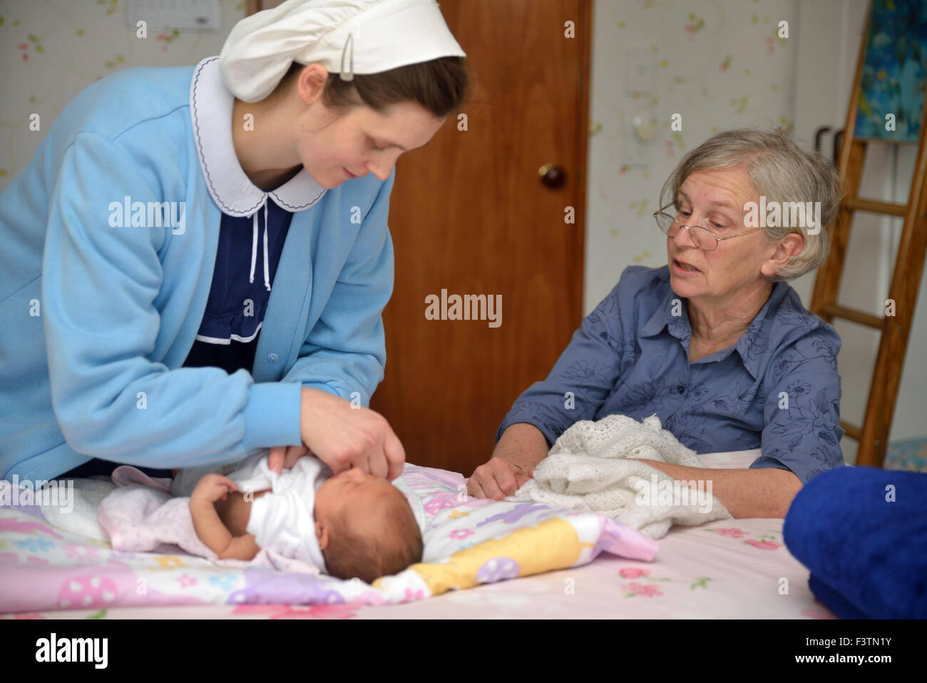 A senior midwife checks a newborn baby with her mother - Stock Image